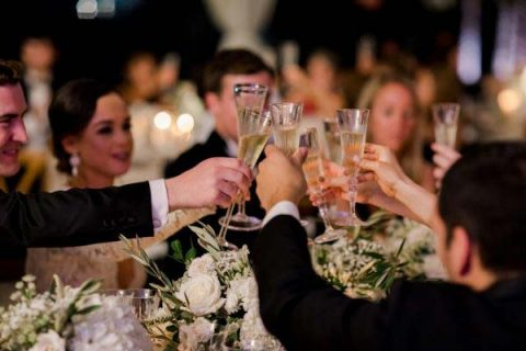 People holding their wine cups in the wedding