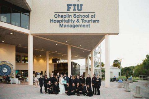 Group of people standing in front of the FIU's Chaplin School of Hospitality and Tourism Management