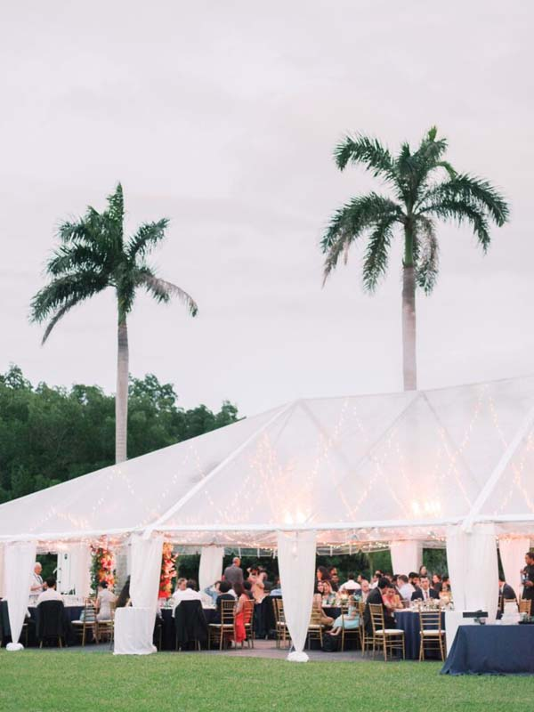 outdoor wedding under large tent next to palm trees