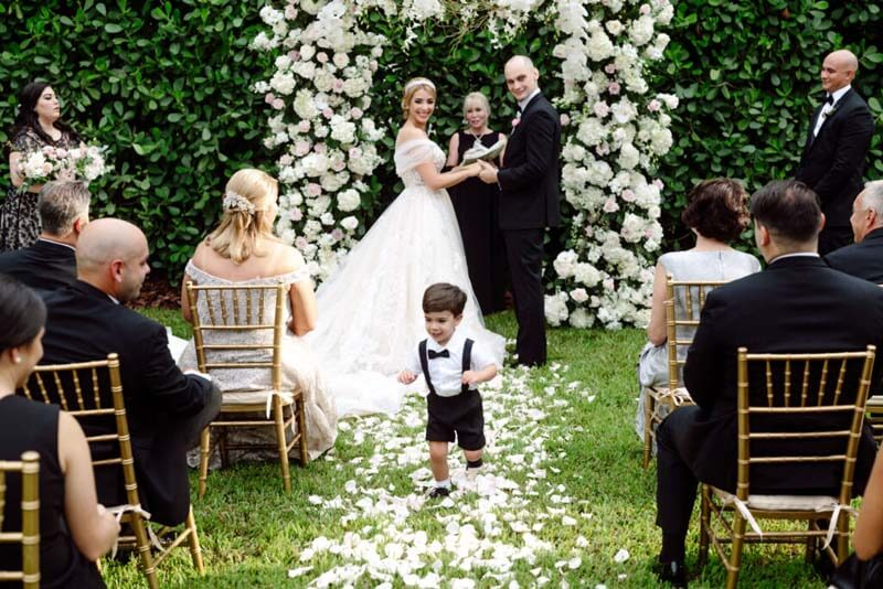 bride and groom at alter and young boy running down the isle
