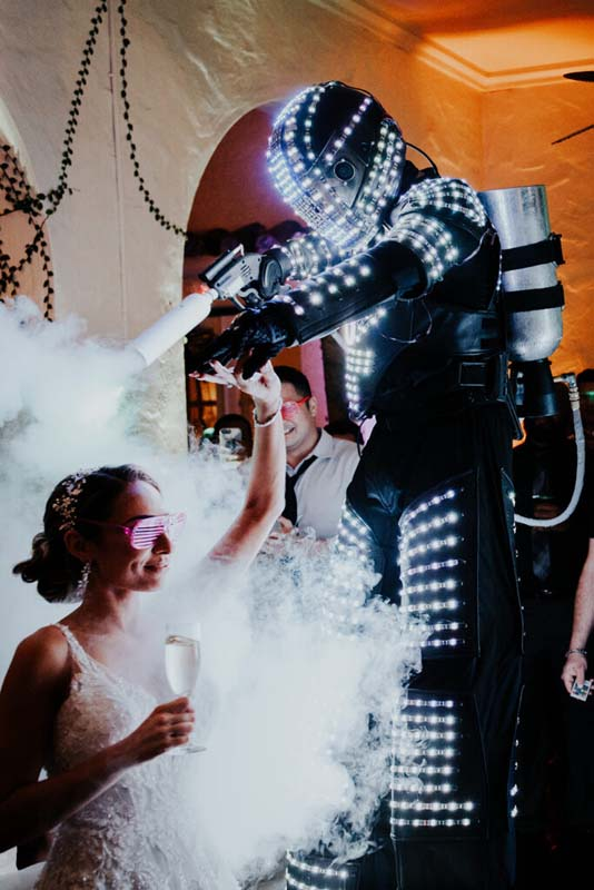 person in futuristic suit and fog gun spraying bride