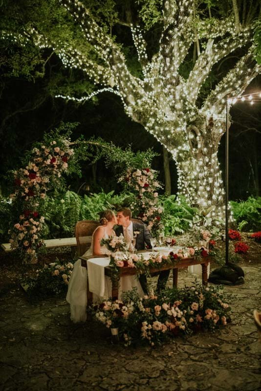 bride and groom kissing under large tree wrapped in lights