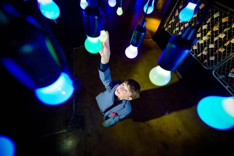 child in suit screwing in lightbulb