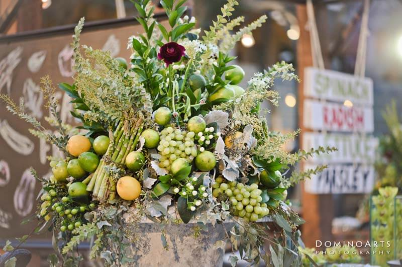 floral center piece that includes various types of fruits and vegetables