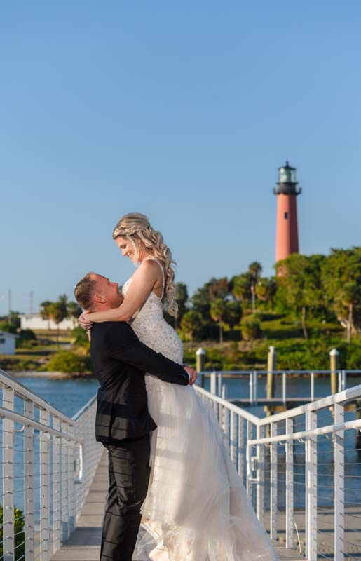 groom holding up bride on dock with lighthouse in background