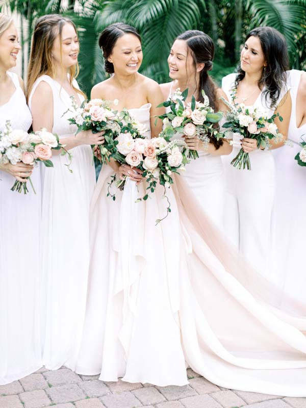 bride and bridesmaids holding bouquets of flowers