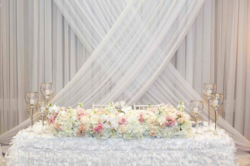 white drapery hung behind sweethearts table with white flowers and table cloth