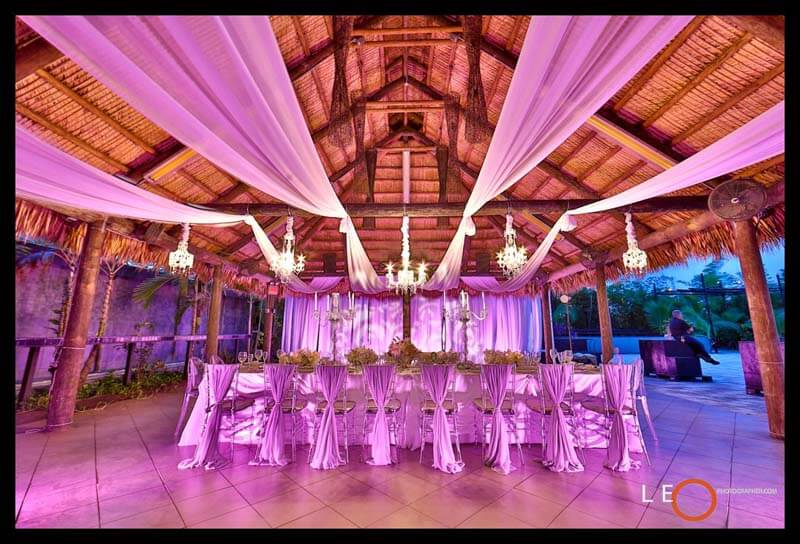 white drapes hung above tables and behind wedding party in cabana wedding venue