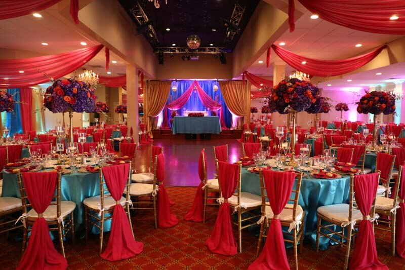 red drapery hung on ceiling and on chairs as well as behind wedding party tables