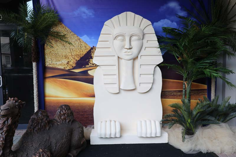 """Egyptian themed decorations with white """"stone"""" sphinx statue and camel statue beside it"""