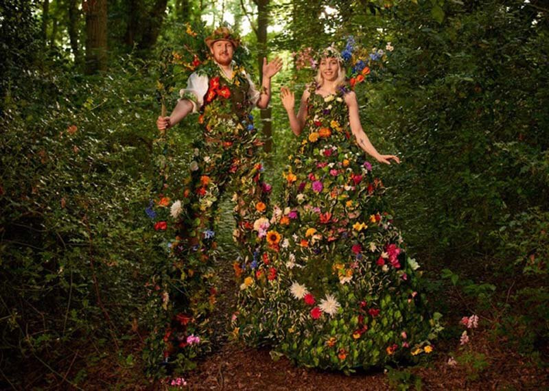 bride and groom dressed in floral outfits on stilts blending into environment