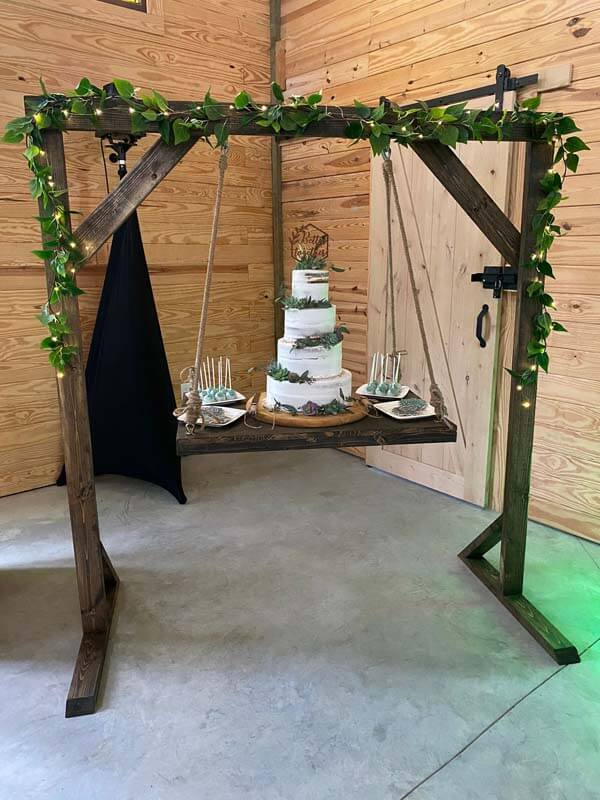 Hanging wedding cake station made of wood with cake and other finger foods