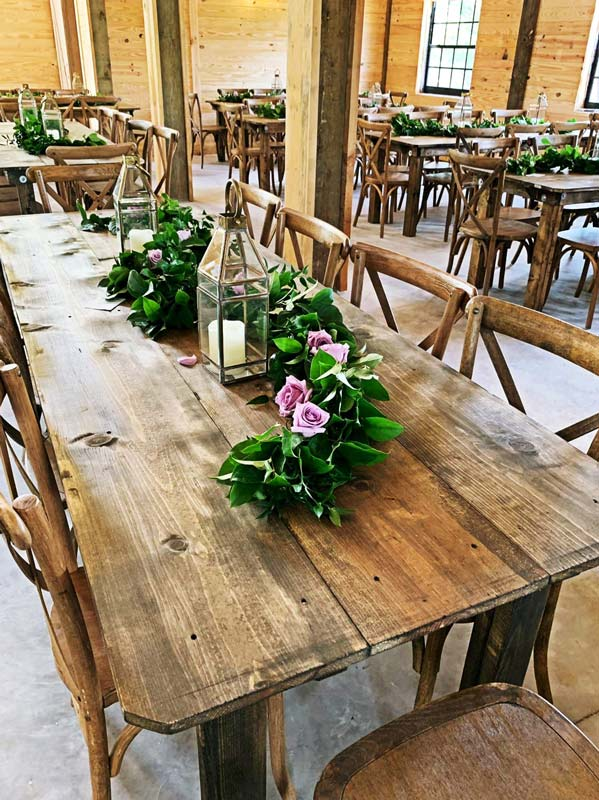 large raw wood table with floral center piece and lit lantern