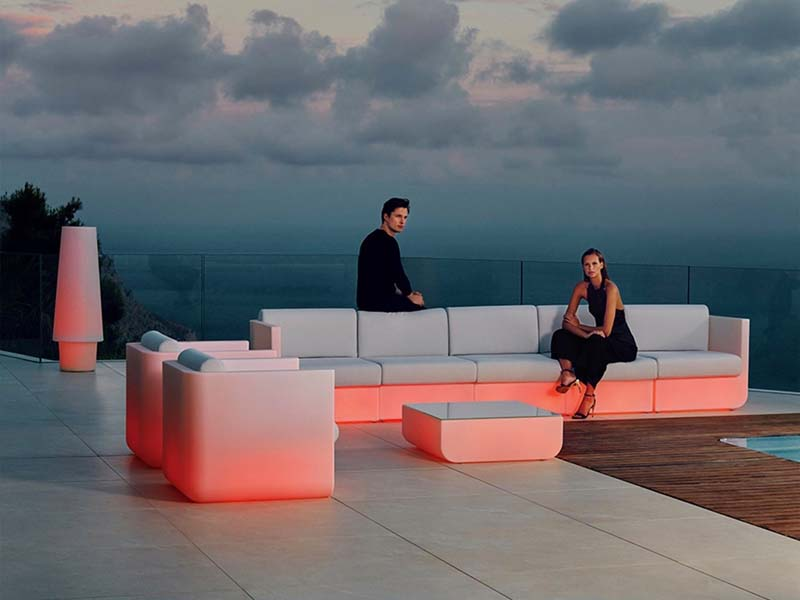 male and female standing in outdoor living space with red lights under furniture