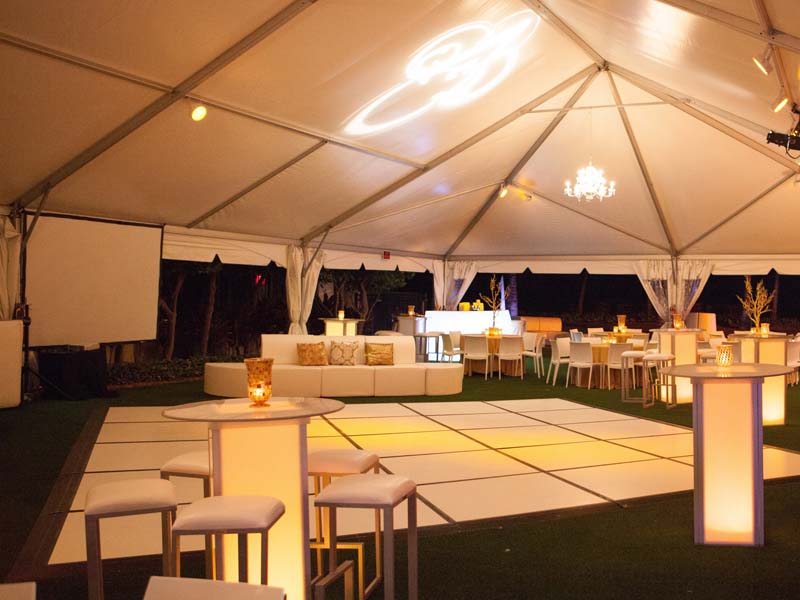 large covered area with dance floor and low lighting and beige colored furniture
