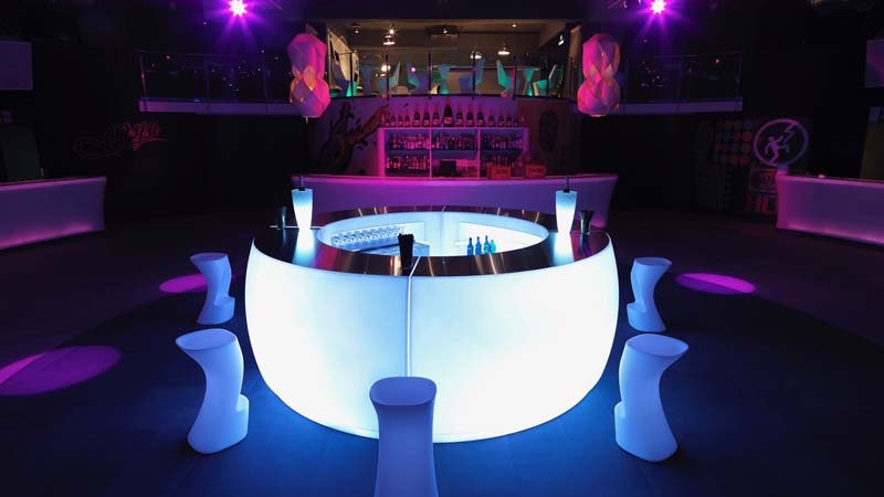 round front lit bar table with white stools