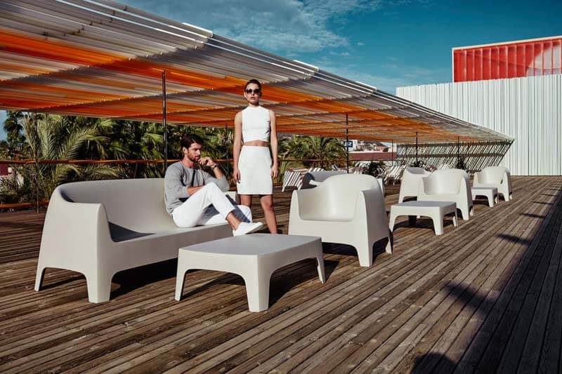 male and female model in outdoor living space with simple outdoor funiture
