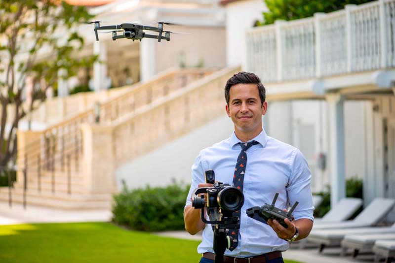 photographer holding camera, drone remote, with drone flying by head