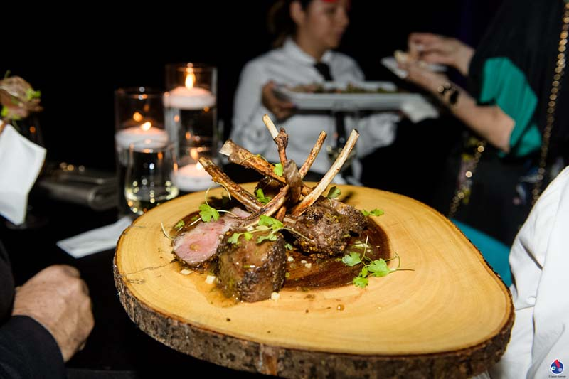 lamb chops being served on wooden disk