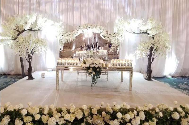 tall white drapes hanging behind large mirror lined with white flowers behind bride and groom table