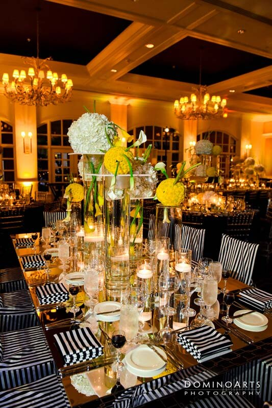 up scale center piece with floating candles and flowers in very tall clear vases