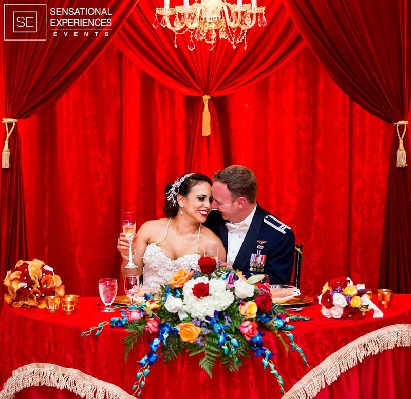 happy bride and groom sitting at their table covered in royal red drapes