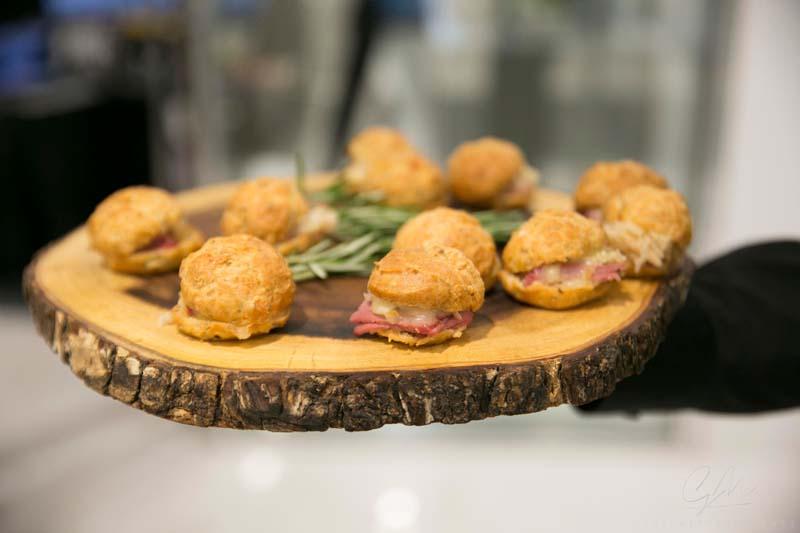 reuben sliders being served on wooden disk