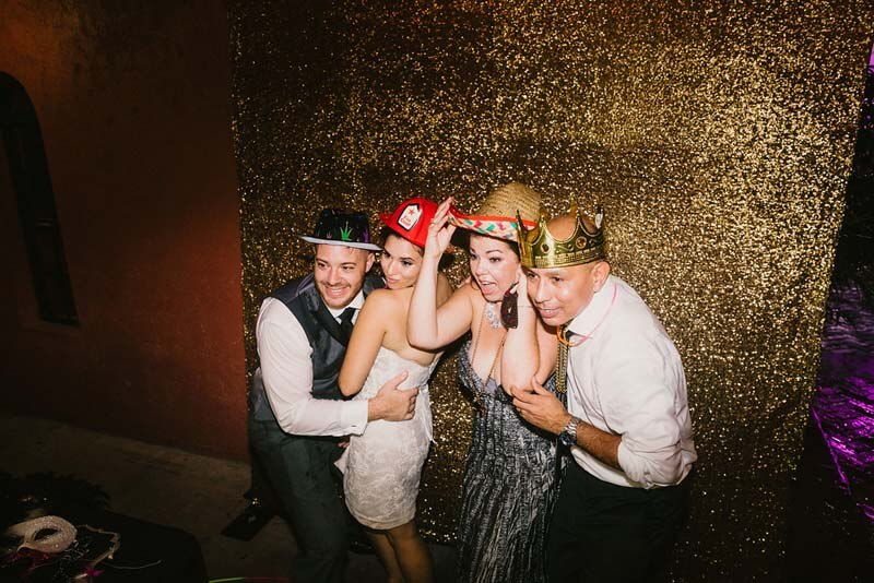 group of 4 wedding guests posing for photo in photo booth