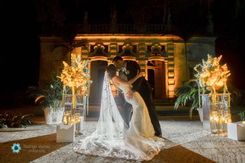 groom dipping his bride and kissing her at night in front of wedding venue
