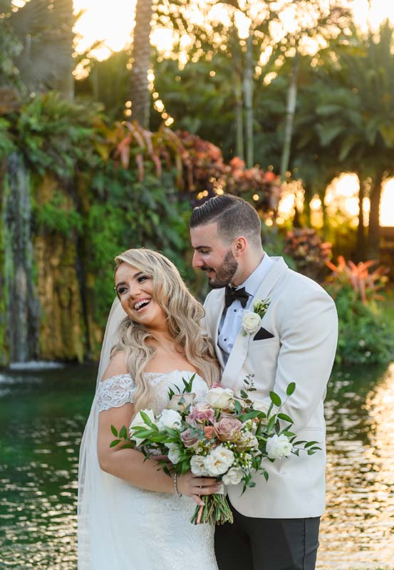bride and groom outdoors by water
