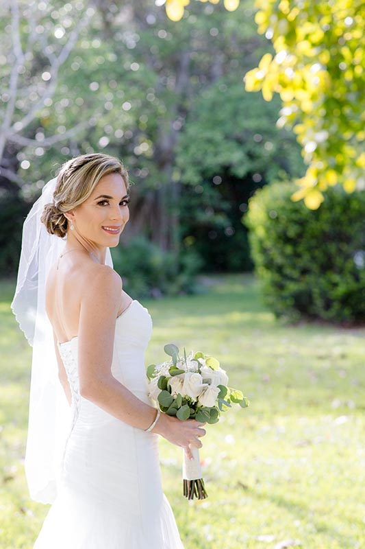 bride outside holding flowers and smiling