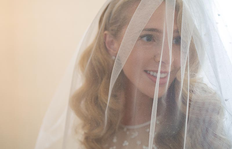 close up of bride with face behind vail