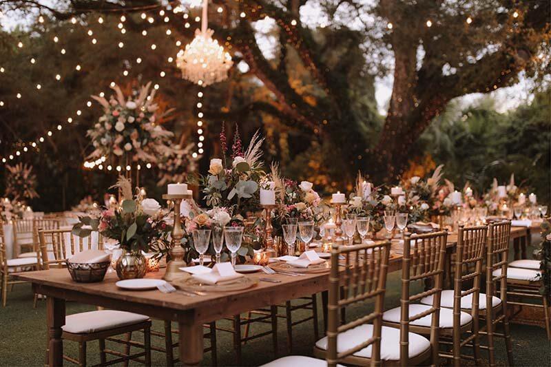 wedding tables set under large tree