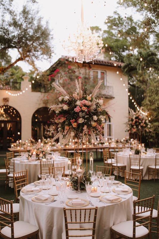outdoor table setting for wedding at twilight with large floral pieces