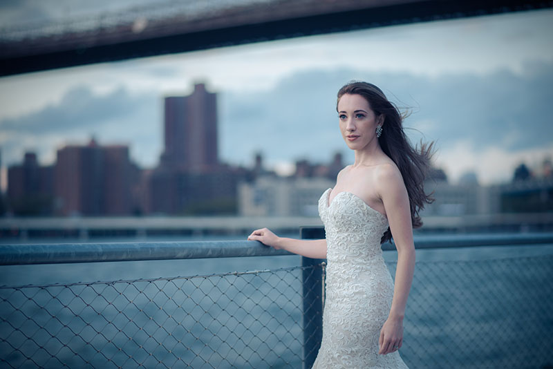 bride standing by fence near large bridge