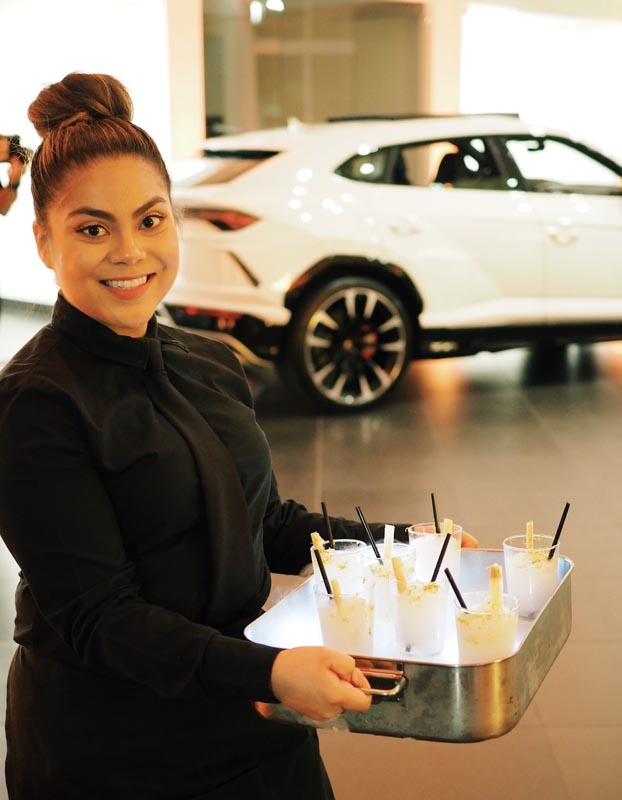 server with tray of drinks heading to a table