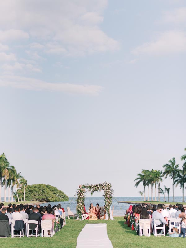 bride and groom sitting by water under flower arch with guests