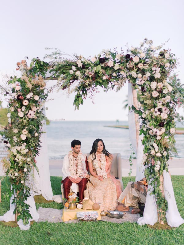 bride and groom sitting by water under flower arch