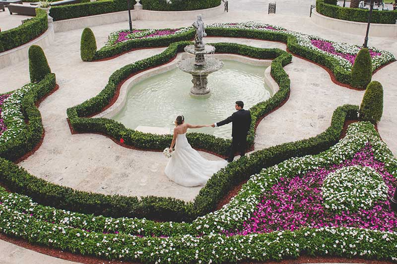 bride and groom holding hands in garden by fountain