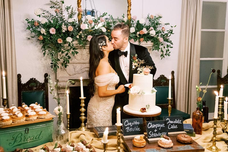 bride and groom cutting the cake and kissing