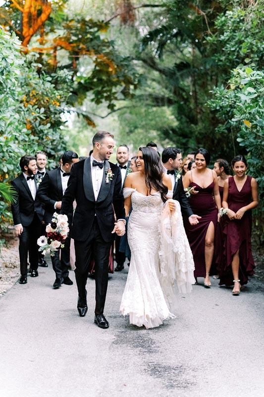bridal party walking outside towards photographer