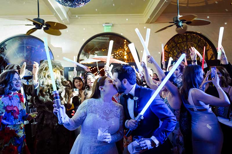 bride and groom with guests holding lightsabers