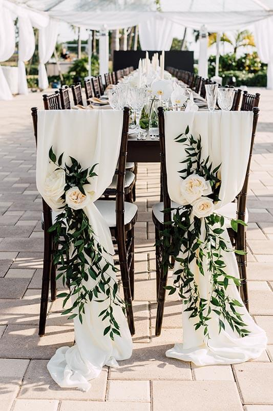 table setting outdoors for wedding with flowers on backside of chairs