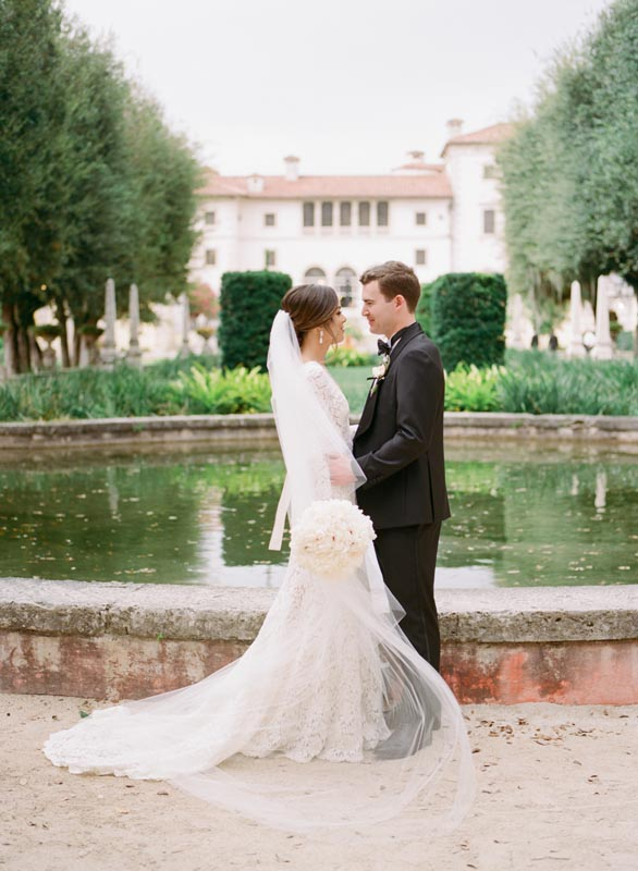 bride and groom embracing next to large fountain