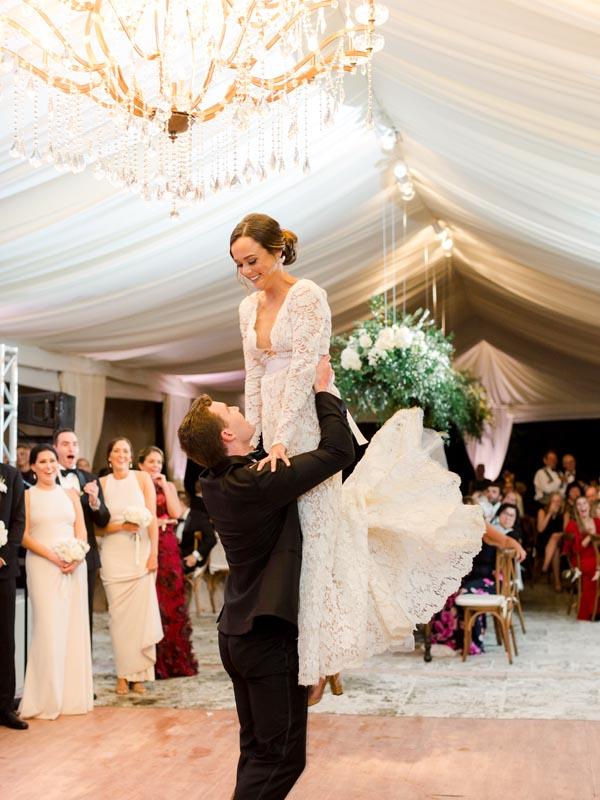 groom holding up wife on the dance floor