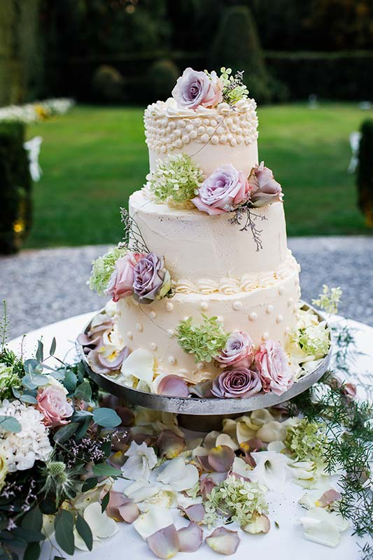 Wedding cake outside. Lots of flowers.