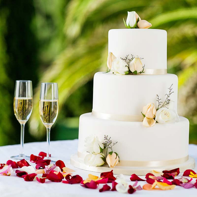 Wedding Cake With Champagne Flutes On Table