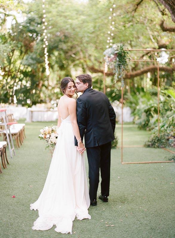 bride and groom - groom kissing wife on cheek