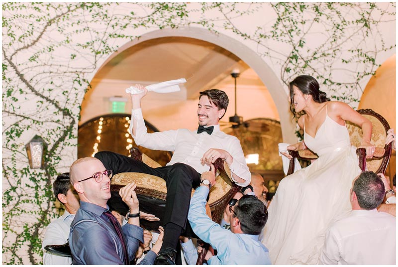 bride and groom being held up in chairs