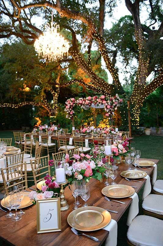 table settings with floral arrangements under large tree